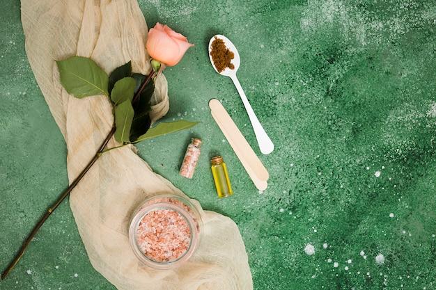 Sal do himalaia-de-rosa no pote; rosa; óleo essencial e café moído na colher contra o pano de fundo texturizado verde Foto gratuita