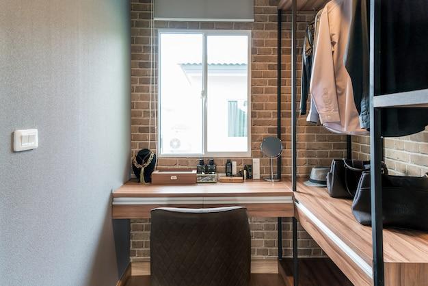 Sala com prateleiras de madeira e vestidos pendurados sob o rack Foto Premium