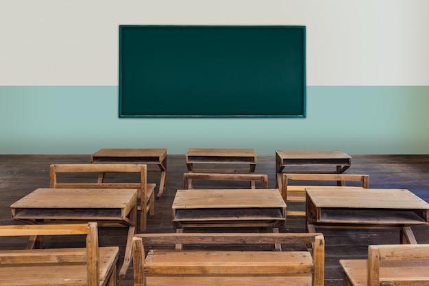 Sala de aula antiga na escola com fileiras de mesas de madeira vazias Foto Premium