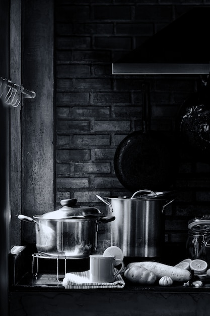 Sala de cozinha com utensílios de cozinha, fogão, exaustor e parede de tijolos com uma xícara de chá de limão com vapor e vapor. conceito da vida do amante do cozinheiro chefe ou do cozinheiro. imagem preto e branca retrô. Foto Premium