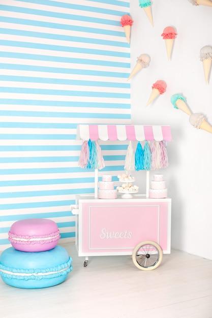 Sala de crianças com faixa azul. zona de fotos de barraca de doces com grandes biscoitos, doces e marshmallows. carrinho com sorvete. quarto decorado para aniversário. carrinho com barra de chocolate. Foto Premium