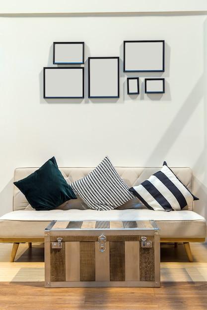 Sala de estar com três travesseiro no sofá de tecido e mesa de fazer baús de aço com parede um Foto Premium