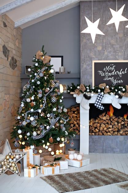 Sala de estar festivamente decorada com lareira com meias de natal. interior de sala de natal em estilo escandinavo. árvore de natal com decorações rústicas, presentes no interior do sótão. decoração de inverno Foto Premium