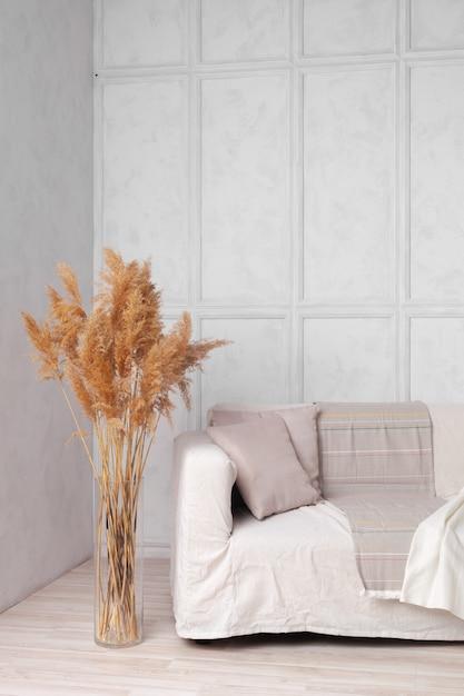 Sala de estilo escandinavo com sofá de tecido, almofadas, manta e planta em um vaso no fundo da parede cinza Foto Premium
