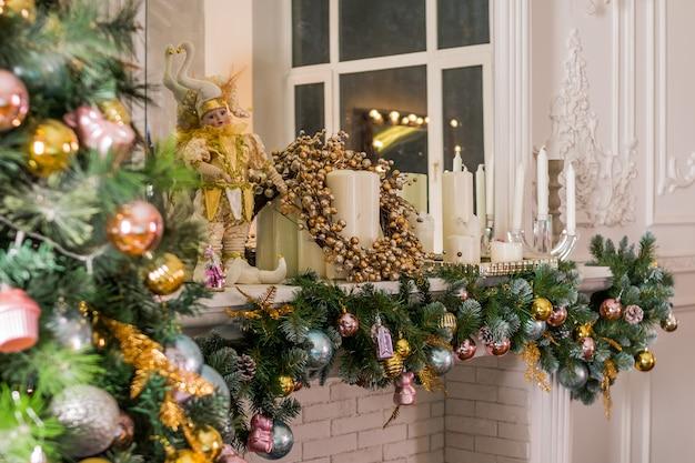 Sala iluminada com luzes decoradas prontas para celebrar o natal. design de interiores de sala de natal, árvore de natal decorada por luzes, velas e guirlanda de iluminação dentro de casa lareira. Foto Premium