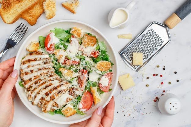 Salada caesar de frango grelhado saudável com alface, queijo, tomate, croutons e molho gourmet Foto Premium