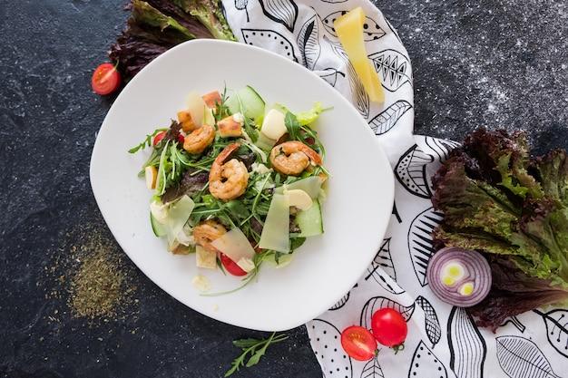Salada caesar fresca com camarões em um prato branco sobre fundo escuro de pedra Foto Premium