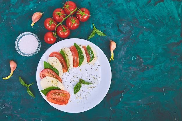 Salada caprese italiana com tomate fatiado, queijo mussarela, manjericão, azeite Foto Premium