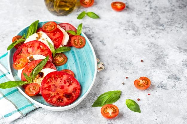 Salada caprese italiana tradicional com tomate fatiado, queijo mussarela, manjericão, azeite Foto Premium