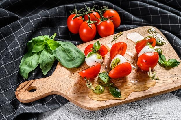 Salada caprese no espeto, tomate, pesto e mussarela. lanche de canapés. fundo cinza. vista do topo Foto Premium