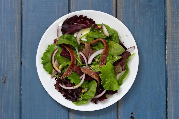 Salada com anchovas e cebola na chapa branca na superfície azul Foto Premium