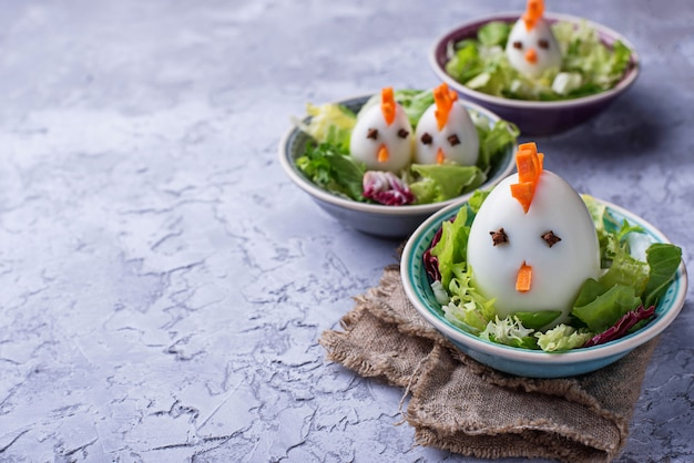 Salada com ovos em forma de galinhas. comida festiva. Foto Premium