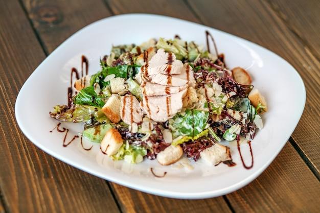 Salada com pepino e galinha e alface em uma placa branca. Foto Premium