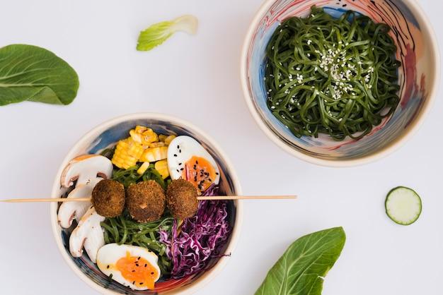 Salada de algas chuka japonês com macarrão em pano de fundo branco Foto gratuita
