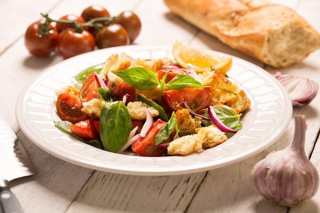 Salada de aperitivo italiano com tomate, pão e bazil Foto Premium