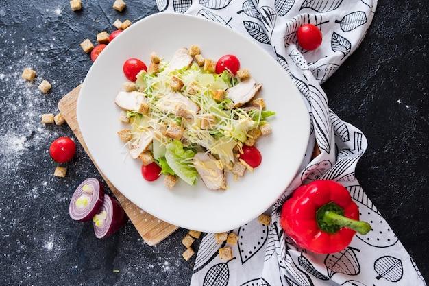 Salada de caesar fresca com galinha em uma placa branca na pedra escura. Foto Premium