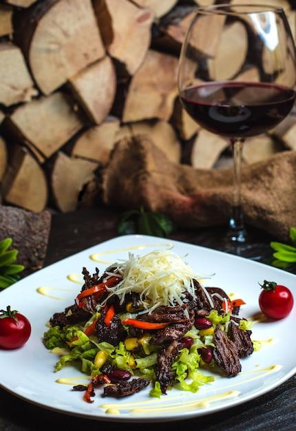 Salada de carne com feijão e um copo de vinho tinto Foto gratuita