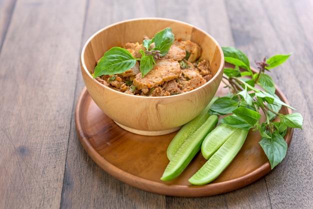 Salada de carne de porco grelhada picante de tradição no estilo do nordeste da tailândia chamado nam tok mho Foto Premium