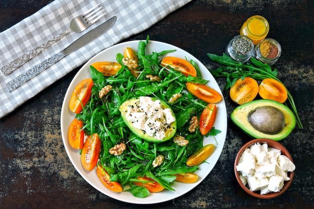 Salada de fitness saudável com rúcula, abacate, queijo feta e tomate cereja amarelo. Foto Premium