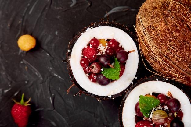 Salada de frutas agrus, groselha, rasbberry em tigela de casca de coco Foto Premium