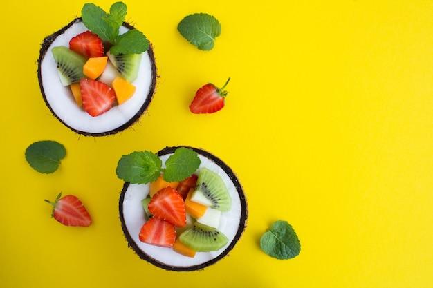 Salada de frutas ao meio coco em amarelo Foto Premium