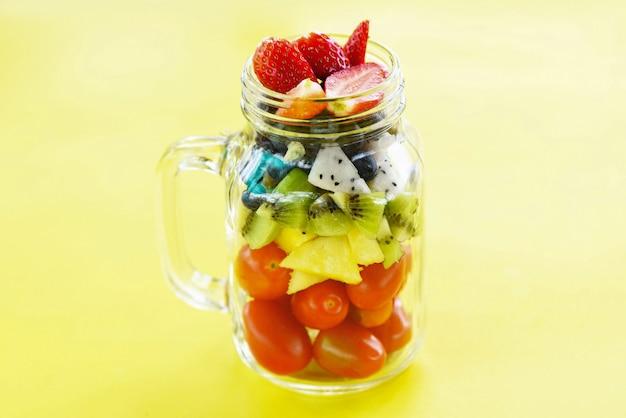 Salada de frutas em um frasco de vidro fresco verão frutas e legumes alimentos orgânicos saudáveis morangos kiwi mirtilos fruta do dragão tomate tropical abacaxi em amarelo Foto Premium