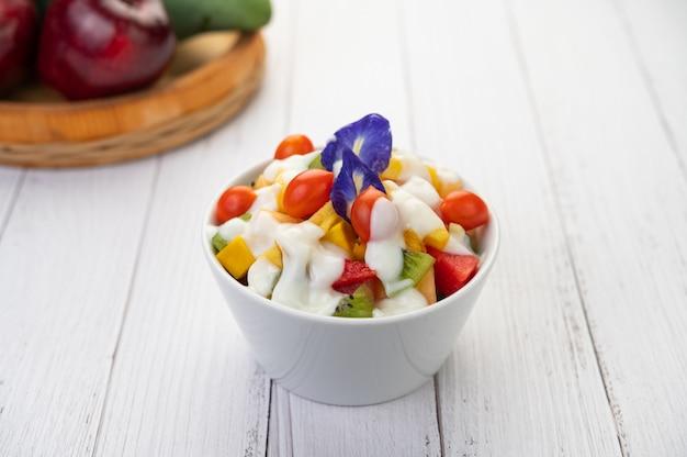 Salada de frutas em uma tigela no chão de madeira. Foto gratuita