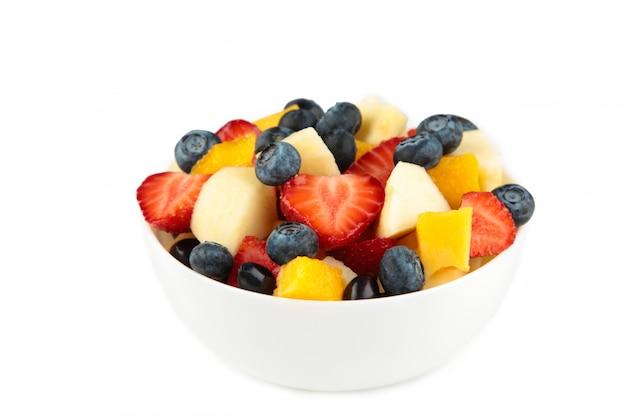 Salada de frutas frescas em uma tigela branca isolada no fundo branco Foto Premium