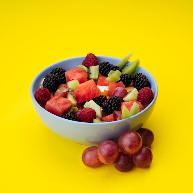 Salada de frutas saborosa em fundo amarelo Foto gratuita