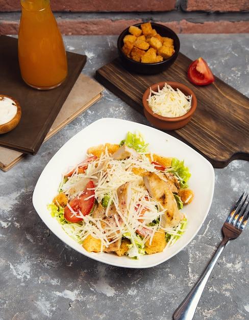 Salada de galinha. frango caesar salad. caesar salad com a galinha grelhada na placa. peito de frango grelhado e salada fresca no prato Foto gratuita