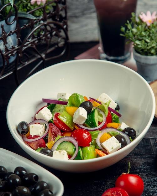 Salada de legumes coberta com azeitonas e queijo Foto gratuita