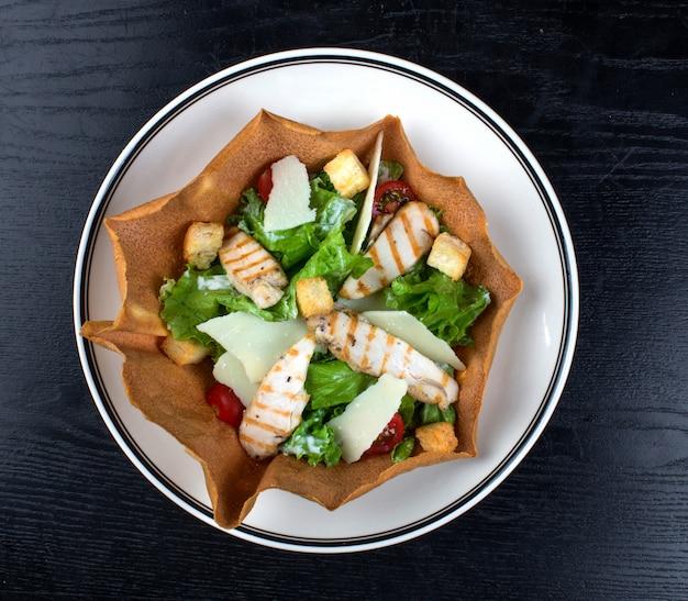 Salada de legumes coberta com peito de frango e bolachas Foto gratuita