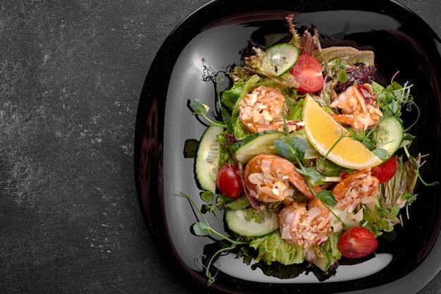 Salada de legumes com camarão, sobre um fundo preto Foto Premium