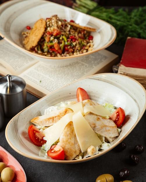 Salada de legumes com frango e coberto com tomate e queijo Foto gratuita