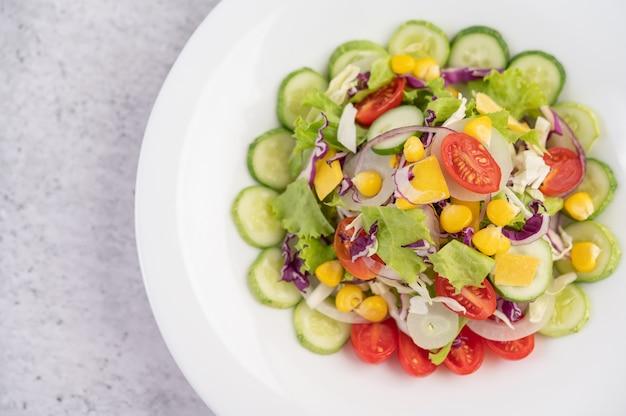 Salada de legumes com ovos cozidos em um prato branco. Foto gratuita