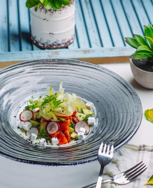 Salada de legumes fresca com rabanete, tomate, pepino, cubos de queijo feta, rúcula Foto gratuita