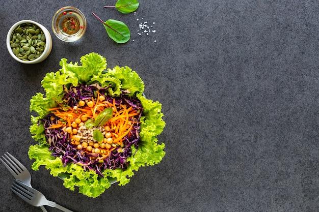 Salada de legumes fresca em um prato preto. vista do topo Foto gratuita