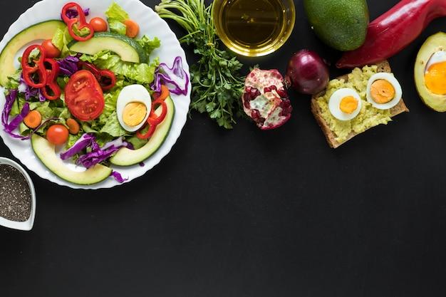 Salada de legumes frescos; pão torrado; frutas; óleo sobre fundo preto Foto gratuita