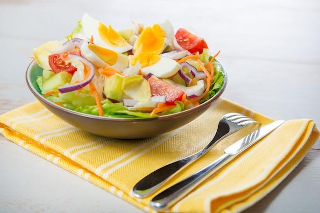 Salada de legumes na toalha amarela Foto Premium
