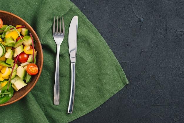 Salada de legumes saudáveis com garfo e butterknife na toalha de mesa sobre o pano de fundo preto concreto Foto gratuita