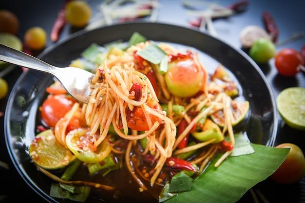 Salada de mamão em um garfo verde salada de mamão picante comida tailandesa sobre o foco seletivo da mesa som tum thai Foto Premium