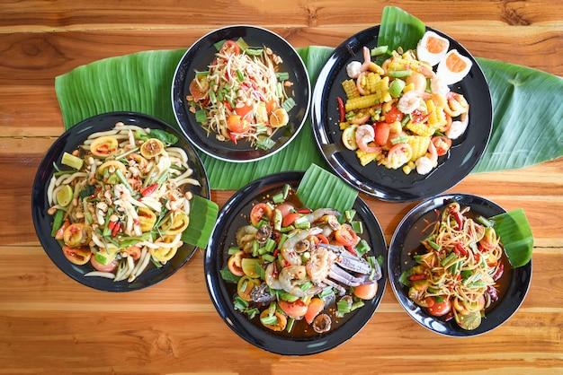 Salada de mamão servida na mesa de jantar comida tailandesa picante de salada de mamão verde no prato com legumes frescos Foto Premium