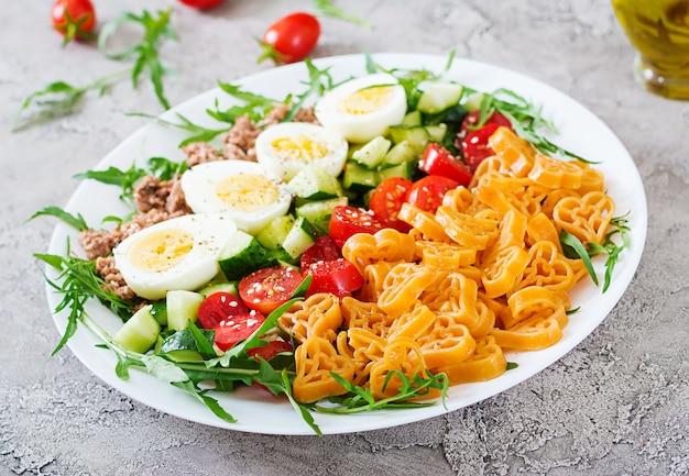 Salada de massa com legumes frescos, ovos e atum em uma bacia branca. comida de almoço. Foto Premium