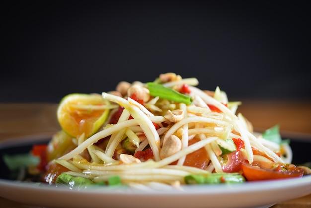 Salada de papaia servida no prato com fundo escuro Foto Premium