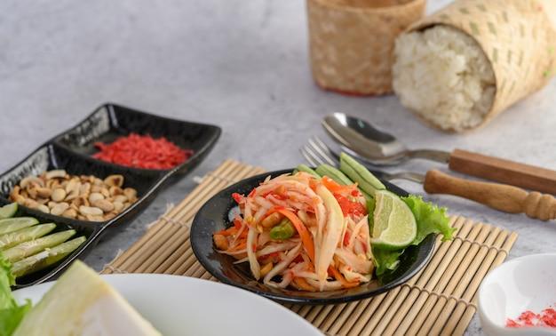 Salada de papaia tailandesa em um prato branco com arroz e camarão seco Foto gratuita