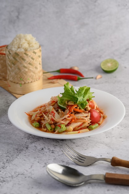 Salada de papaia tailandesa em um prato branco com arroz pegajoso Foto gratuita