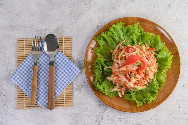 Salada de papaia tailandesa em uma placa de madeira com talheres Foto gratuita
