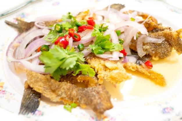 Salada de peixe gourami crocante picante com manga verde, comida tailandesa Foto Premium