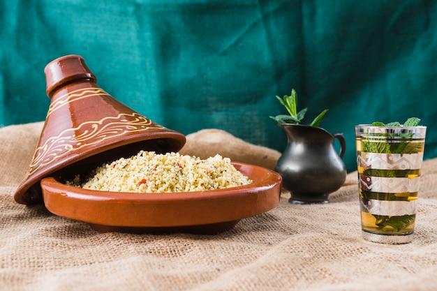 Salada de quinoa perto de xícara e jarro na serapilheira Foto gratuita