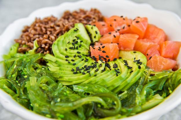 Salada de salmão, abacate, arroz integral, algas marinhas. Foto Premium